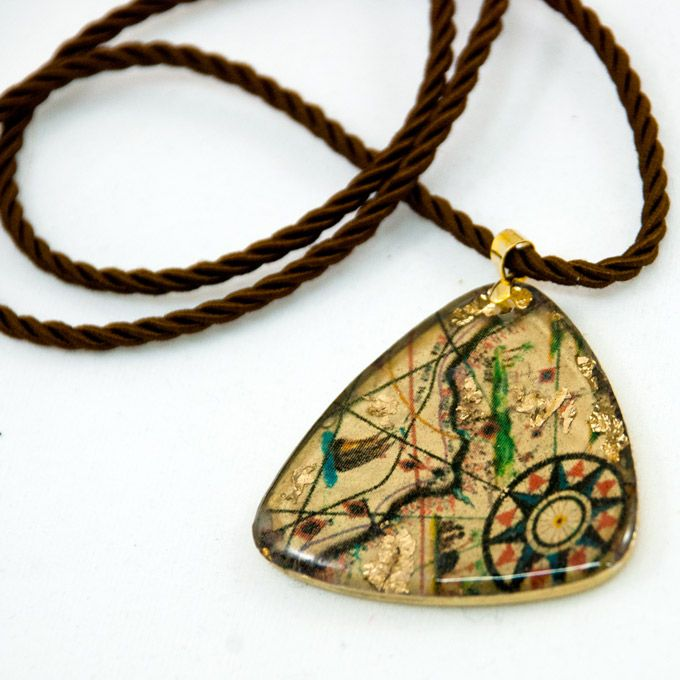 Maps Necklace with gold leaf, resin and silk cord.