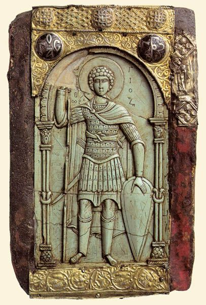 St.George. 11th cent. Steatite Icon. Vatopedi monastery, Athos, Greece George is depicted as a cavalry officer. He wears a klivanion cuirass (lamellar) with attached metal pteruges and a mail upper part-probably a hood. His long leg protection (kampotouva) and tunick betray that he belongs to a cavalry regiment. A spear, a long sword and an almond shaped shield are the saint's weapons.