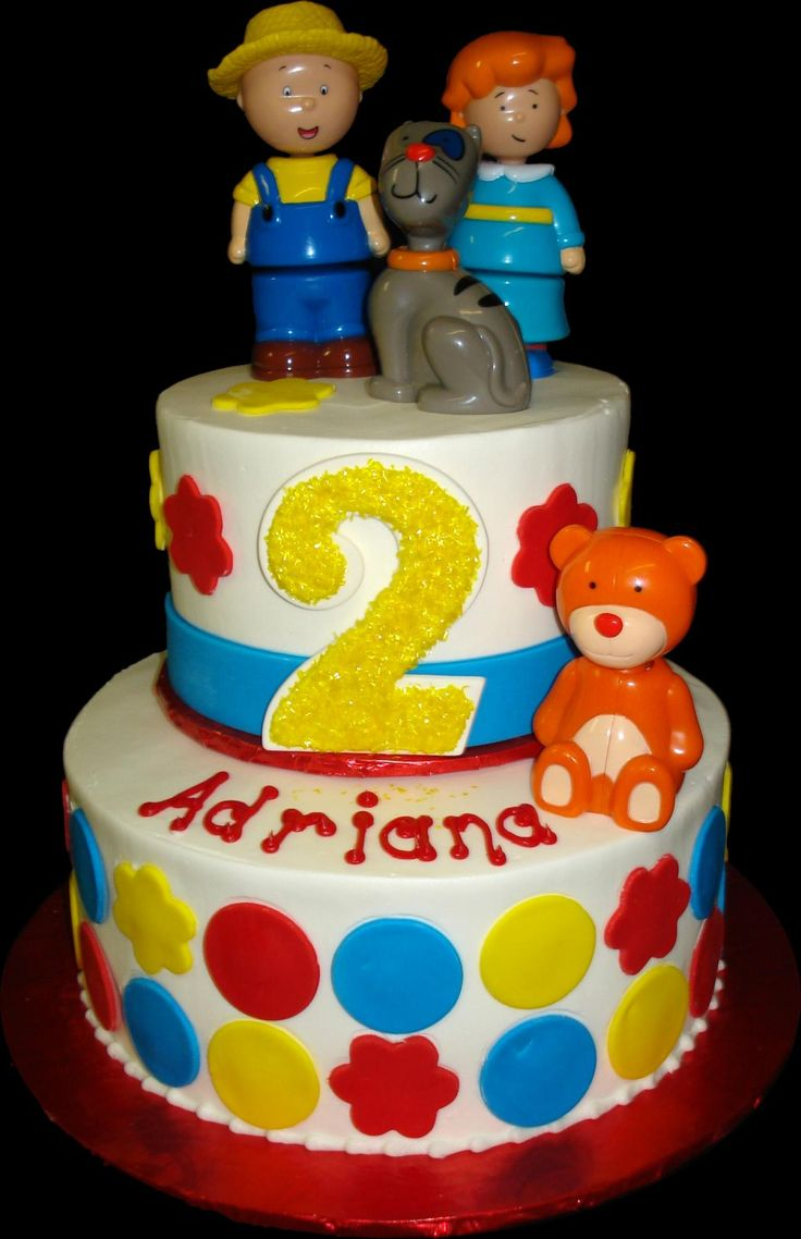 Caillou 2nd Birthday Cake. White buttercream iced, round 2 tiers decorated with circles, Caillou, Rosie, Gilbert, and Teddy Bear. Everything on this cake is edible. (Plastic character figurines provided by client.) (Serves 28-55 party slices.)
