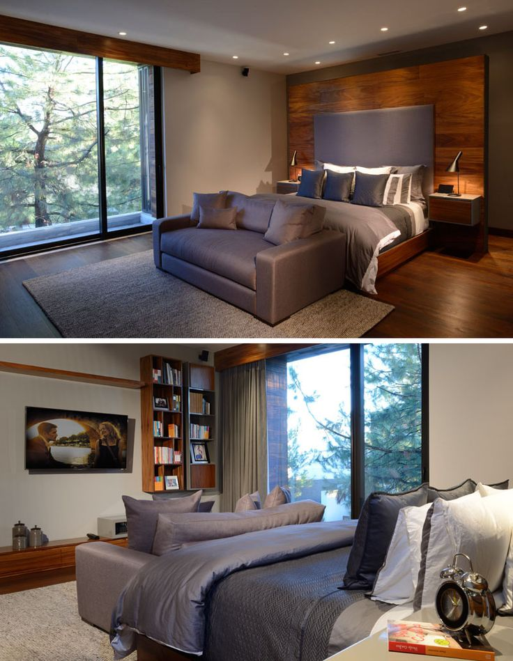 This master bedroom has a large standalone feature wall behind the bed, and opposite the bed, there are bookshelves and storage that match the wooden feature wall.