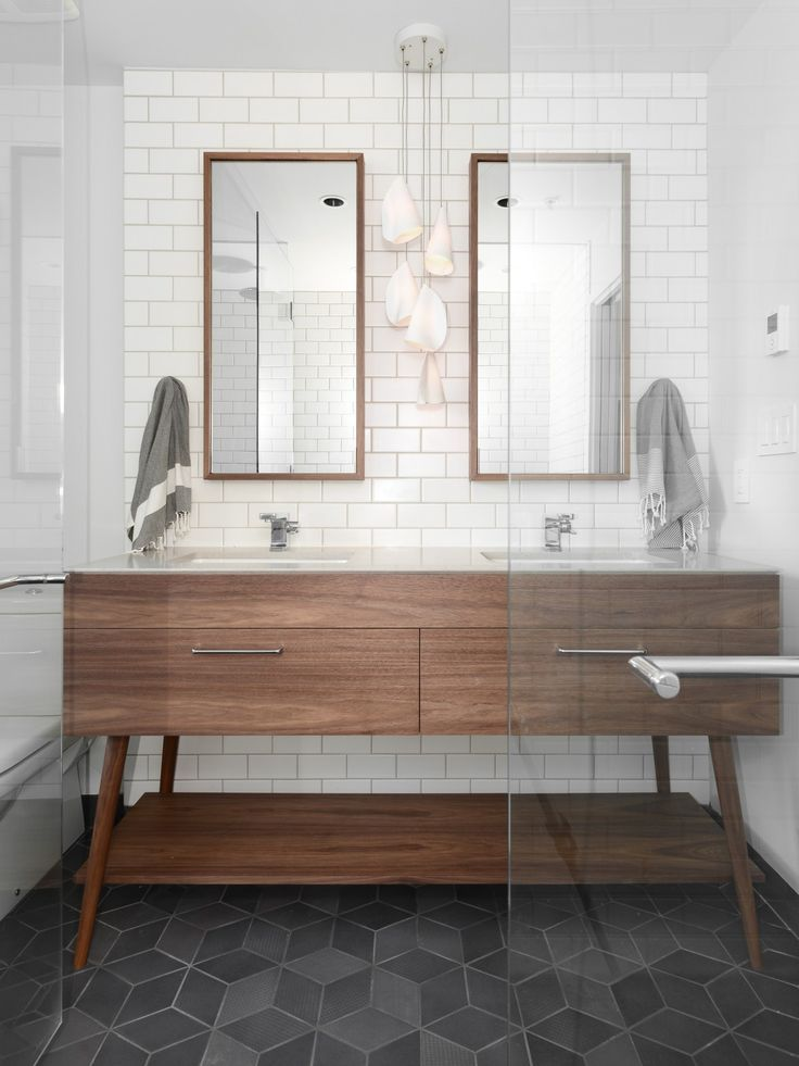 gorgeous modern bathroom with mid century vanity, slate geometric tile floors, and seamless glass shower door