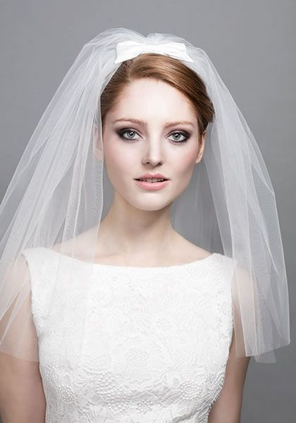 the dress looks nice with a simple bow and a short veil. maybe run with this idea?