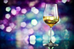 Glass of white wine against a glowing bokeh - copy space, select Stock Images