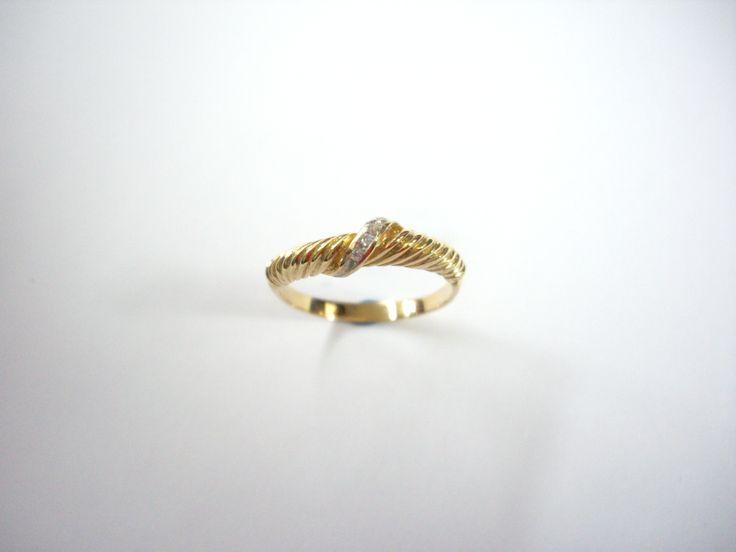 Delicado anillo en oro amarillo con cintillo central en diamantes