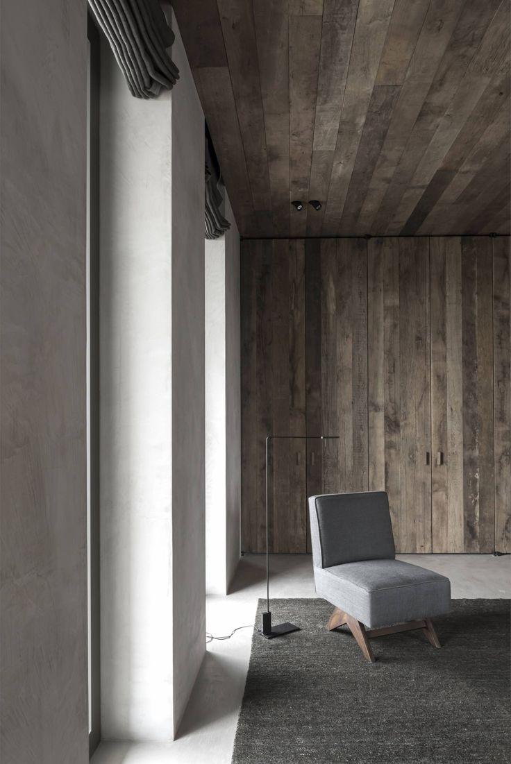 Reconciliation of wooden walls and typical modernist furniture. Asymmetric lamp a nice addition. Like the shade of grey on the sofa - minimal but comfortable