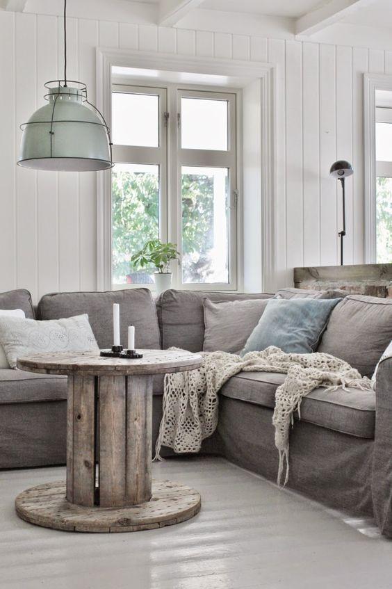 deco industrielle dans un salon, touret bois table basse, canapé gris, coussins décoratives, suspensions industrielles, lambris blanc