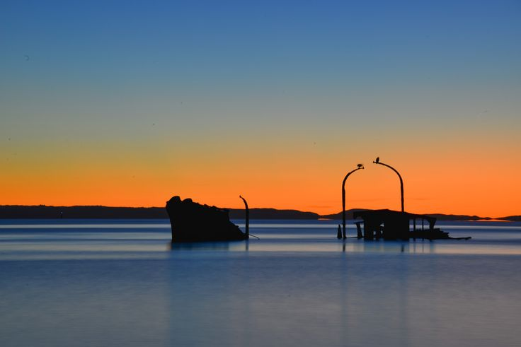 Silhouette of shipwreck at sunset. Tangalooma wrecks, Merton Island, Queensland, Australia
