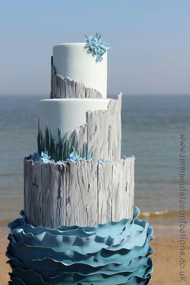 This laid back beach themed cake is just perfect with it's drift wood grained tiers and soft grey, blue and white.