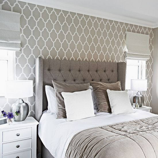Traditional grey bedroom with patterned wallpaper and headboard