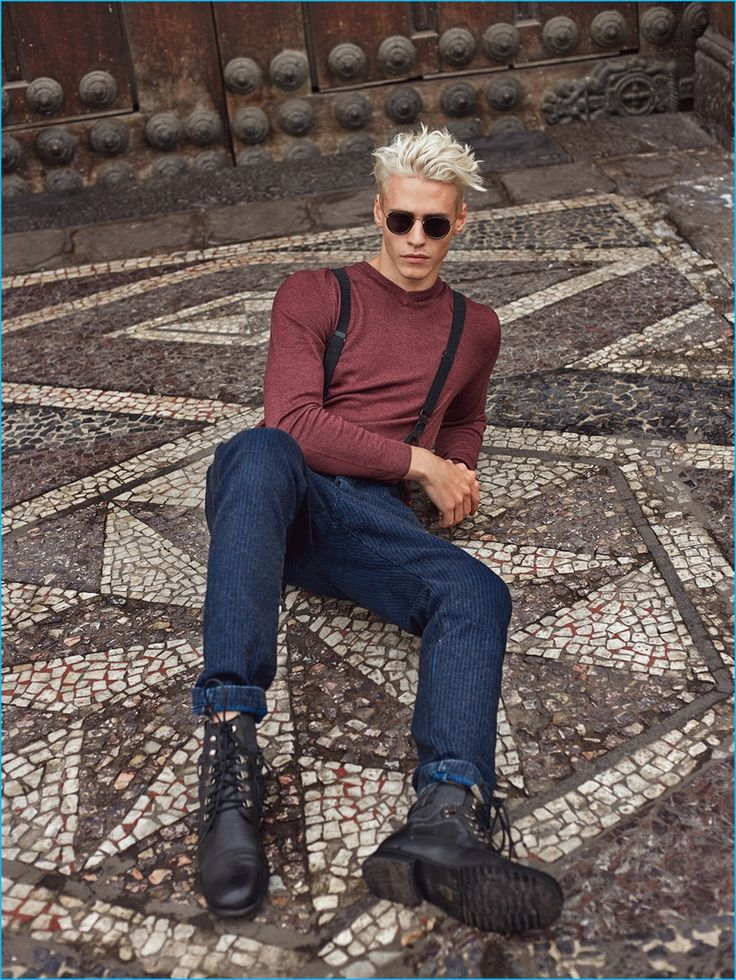 Model Oliver Stummvoll goes casual in a Ralph Lauren sweater, Diesel denim trousers, Ray-Ban sunglasses, and Giorgio Armani boots.