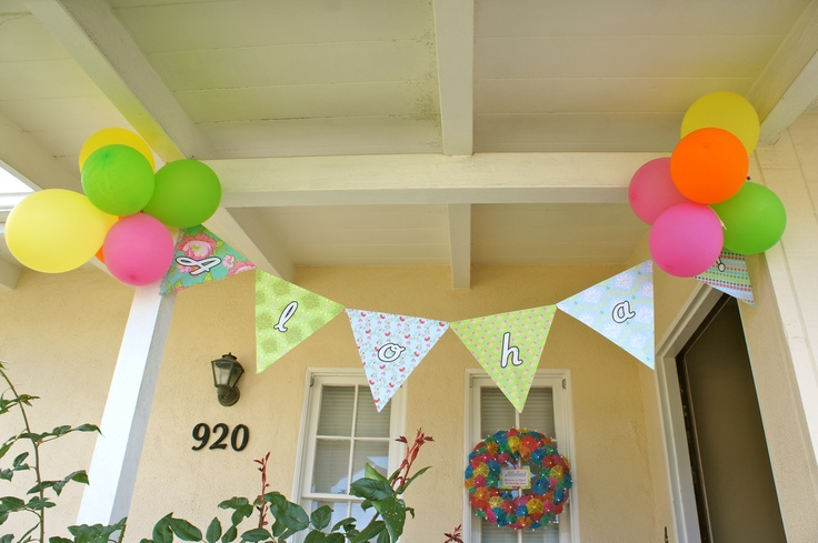 birthday luau - homemade paper banner and cocktail umbrella wreath outside