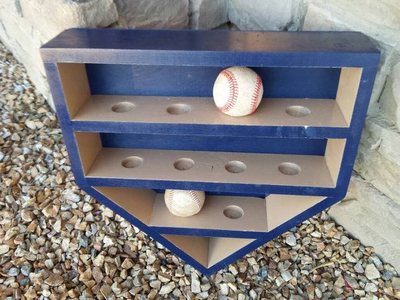 Handmade home plate baseball holder. Customize to your favorite team colors. Wall hanging shelf. Has 10 hole slots that will hold 10 baseballs. 17 inches wide by 17 1/2 inches long. About 4 inches deep. Has backing to it and includes hooks to hang it. Any questions please dont hesitate to ask. Stain & color of wood can be customized. Message me for any inquiries.