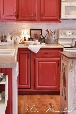 .I've always wanted rustic red cabinets and a wooden floor. Also love the distressed kitchen island. {sigh}
