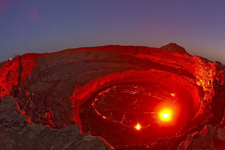 Erta Ale sopka, November 2009: Sopky s jeho láva jazero - The red glow of the lava illuminates the crater walls under the blue sky of dusk. A small group of o...