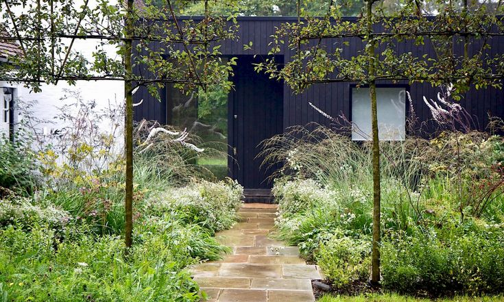 We take a walk through a gatehouse courtyard in London's Stoke Common Nature Reserve, inspired by shou sugi ban, in Gatehouse Garden: A Dramatic Black Backdrop for a White Wildflower Meadow. Photograph by Rosangela Photography, courtesy of Stefano Marinaz Landscape Architecture.
