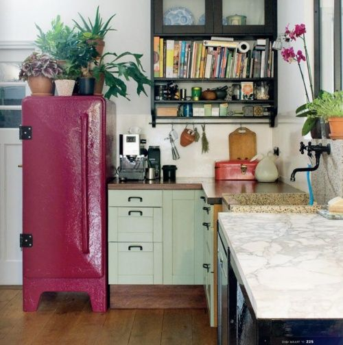 Eclectic chic kitchen with an eye catching retro raspberry colored fridge! Gorgeous potted indoor greenery too.