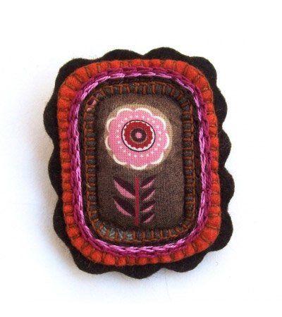 Virágos hímzett kitűző  Kis, rózsaszín hímezett virág kitűző, barna filc alapra felvarrva. Barna, rózsaszín és narancssárga színekben pompázó, finom darab.