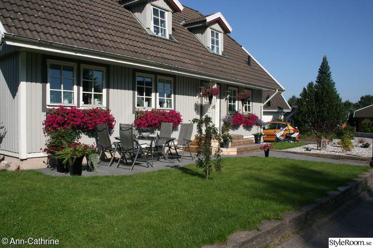 hus med blomlådor under alla fönster och gräsmatta
