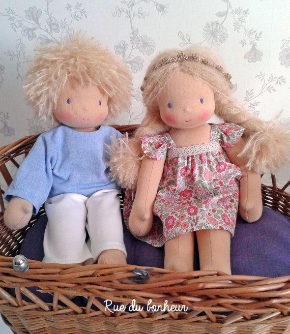 Commande pour deux poupées personnalisées de taille moyenne (35 cm), un poupon et une poupée, couleur de peau pêche clair. La couleur des cheveux et des yeux est à choisir lors de la commande. (Sélectionnez le coloris que vous souhaitez ci dessus dans les 2 onglets prévus à cet effet).  Chaque poupée comprend une tenue :  - Pour le poupon une chemise, un pantalon et un caleçon. - Pour la poupée une robe liberty et une petite culotte. Vous pouvez choisir la couleur des habits ainsi que votre…