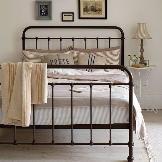 Wrought iron bed frame with eclectic gallery wall above the headboard.