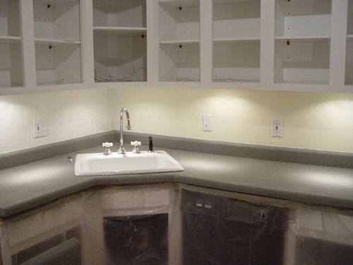 spray painted kitchen counter tops! quick and inexpensive fix that we might just need to try...