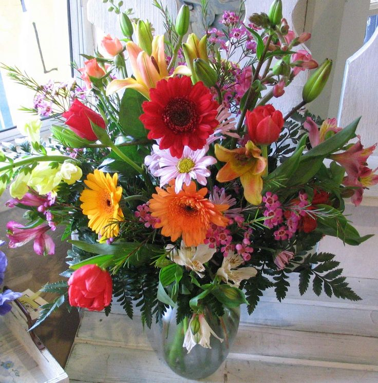 Different colored flower arrangements with pretty vase for A lot of different flowers make a bouquet