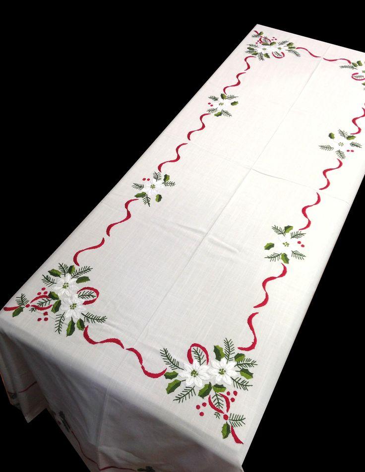 Mantel de Navidad bordado a mano, con un diseño de flores blancas con lazos rojos y vainica en el embozo.  De fácil planchado. Se puede usar legía de color. 12 Servilletas incluidas con el mantel.  Para otras medidas consulte sin compromiso en http://www.lagarterana.com/