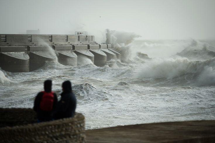 IlPost - Brighton, Inghilterra - Una+coppia+osserva+le+onde+infrangersi+contro+una+parete+della+Marina+di+Brighton+durante+un+temporale.+La+Gran+Bretagna+è+stata+colpita+dalla+peggiore+tempesta+degli+ultimi+dieci+anni,+con+forti+piogge+e+venti+a+più+di+130+chilometri+orari (LEON+NEAL/AFP/Getty+Images)