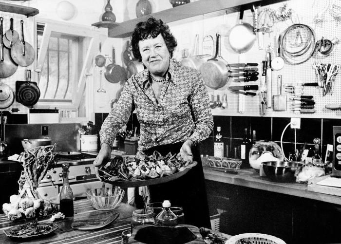 Julia Child in her kitchen with background of pots and pans hung on pegboards