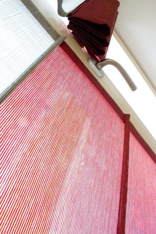 Particolare di tende a pacchetto a vetro di tipo radiale a settori di colori differenti in tessuto d'organza sovraffilata con nastrini in raffia. Realizzato da Tappezzeria Semenzato di Mestre