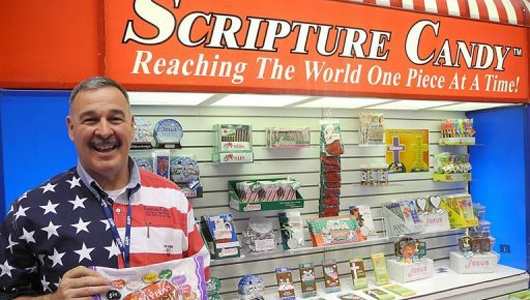 """SCRIPTURE CANDY: Founder Brian Adkins poses at his booth at the Sweet and Snack Expo. The Alabama-based company aims to use moments of sweet indulgence to preach the gospel. """"Our mission is to reach the world one piece at a time with the word of God and it just happens to be on a piece of candy,"""" Adkins said. (Photo: Mira Oberman/AFP)"""