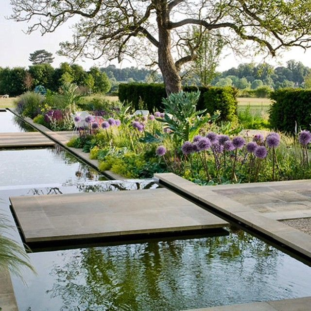 A contemporary country garden designed by Marcus Barnett, with cleverly designed stepped water feature traversed by wide walkways and planted with big blocks of strong form plants like allium and artichokes.Image from his website