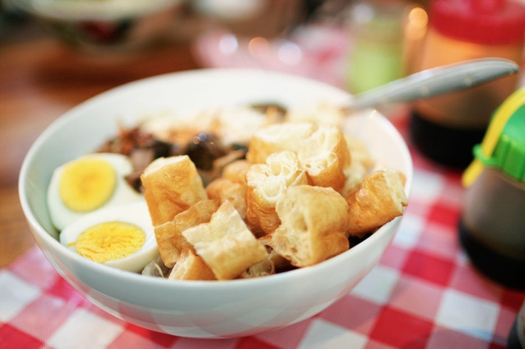 Pieces of Cakwe, chunks of boiled egg, shredded chicken and all other toppings covering the delicious rice pouridge, creates the sensational taste of Bandung's Bubur Ayam.