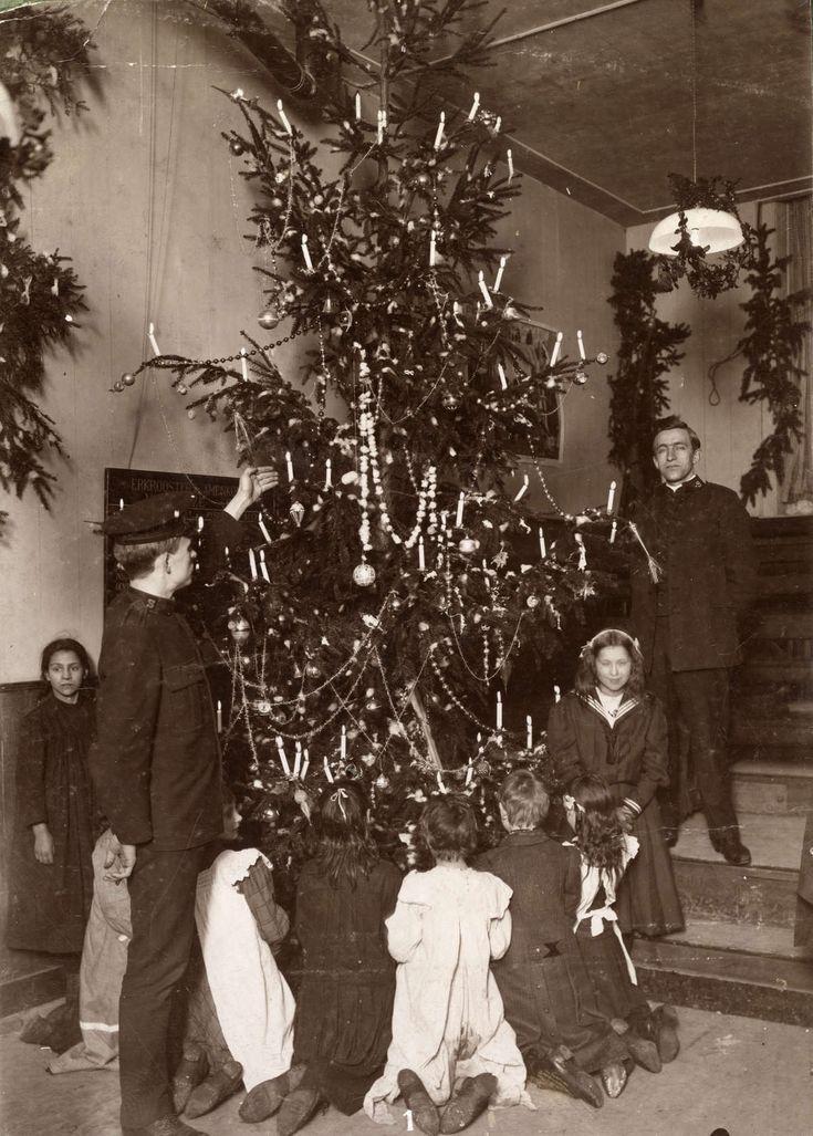 Leger des Heils : Kerstboom in lokaal van het Leger des Heils met eromheen geknielde kinderen en een paar heilsoldaten tijdens kerstviering. Nederland, Amsterdam, 1911.