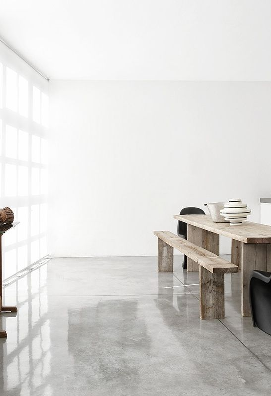 The stark Polished concrete floor with warm rustic furniture.