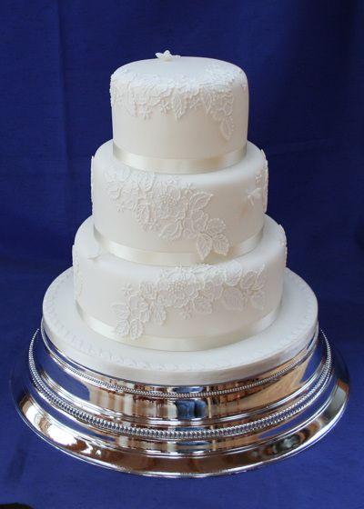 Torta de boda decorada con apliques de encajes y cintas. #TortaDeBodas