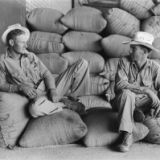 """""""Farmers sitting on bags of rice, state mill, Abbeville, Louisiana"""" (1938)"""