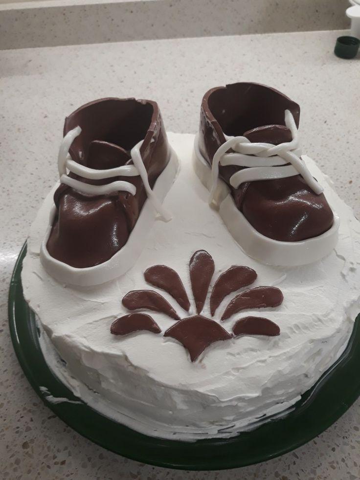 Torta con panna ripiena di crema con scarpe da tempo libero di pasta di zucchero bianca marrone.