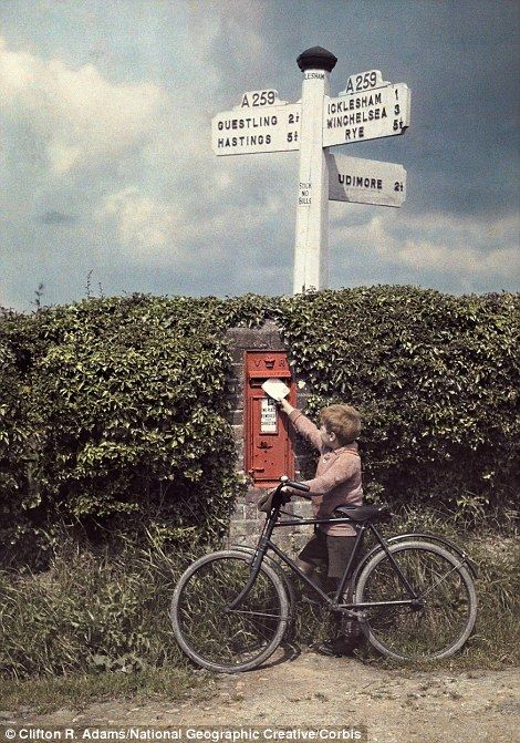 November 1928, England: A little boy mails a letter in a postbox in the hedgerow..in Sussex.