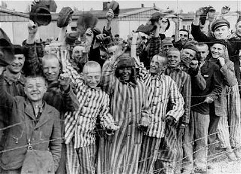 Liberated Dachau prisoners cheer on U.S. troops. 1945