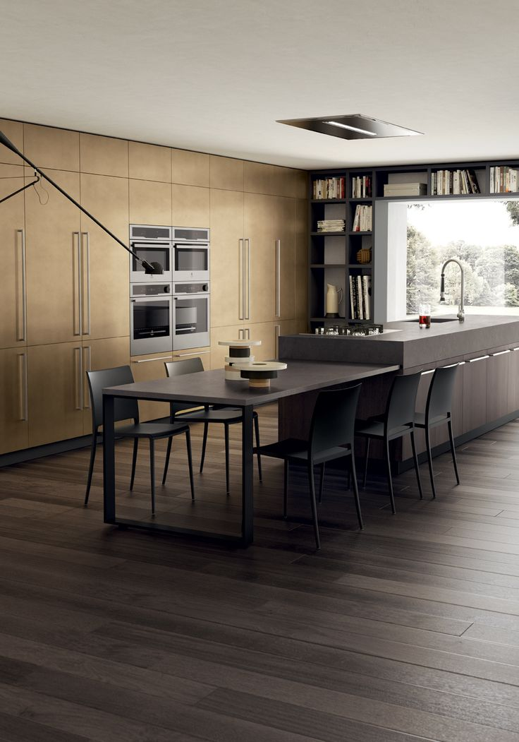 A colour variant for this composition, marked by the stained look lacquered fi nish in Stained Brass colour on the tall units fi tted with vertical and horizontal handles. Twin ovens and a double refrigerator are all strategically incorporated into the cabinets to exploit the available space with skill. Dark contrasting tones mark the island, with Saxony Walnut doors, as well as the worktop and table-height top, the plinth and the Hold Up support.