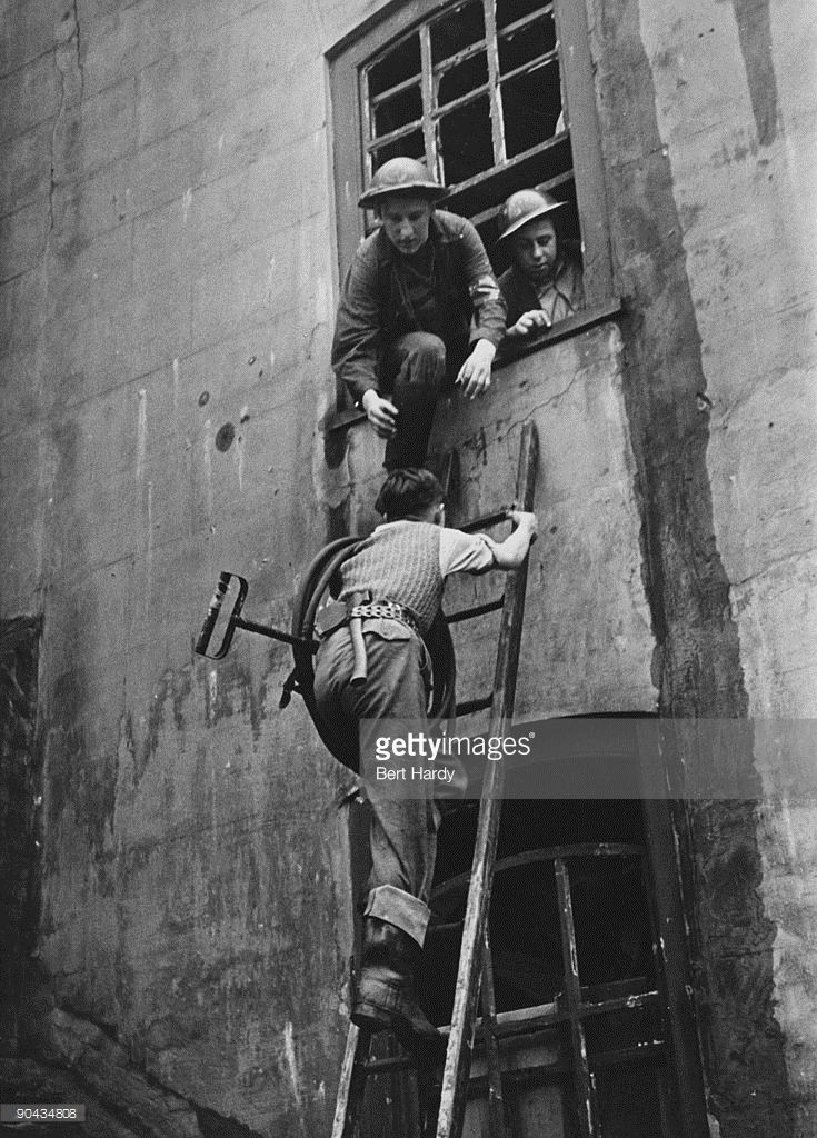 boy-carrying-a-stirrup-pump-up-a-ladder-to-tackle-a-fire-after-an-air-picture-id90434808 (735×1024)