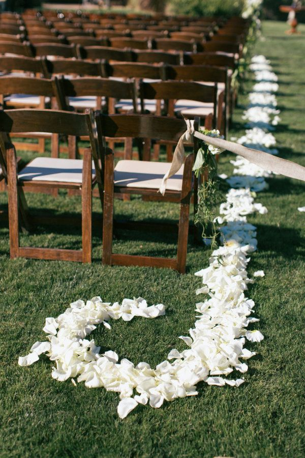 Instead of decorating the entire aisle, consider placing the silk rose petals on the side.