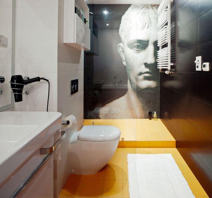 Nowoczesna łazienka już na etapie projektu miała założenie, aby zmieścić w niej prysznic i wannę. Biało-czarną bazę w łazience ożywia pomarańczowy, a oryginalna mozaika w formie portretu Napoleona podkreśla niezwykłość nowoczesnej łazienki.