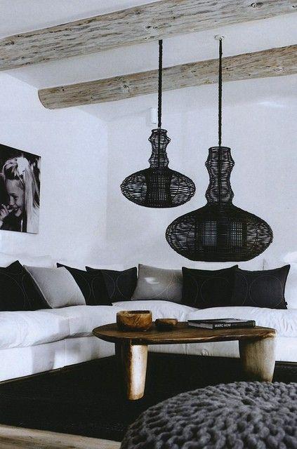 Salón decorado en blanco y negro. La calidez la aporta la mesilla central y las vigas de madera. Las lámparas son un detalle muy original.