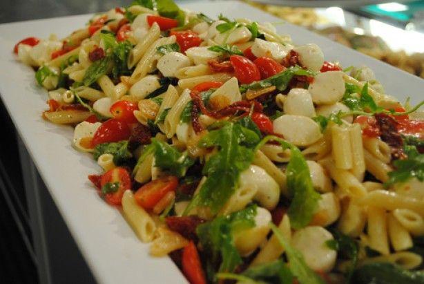 Salade gemaakt van pasta, zongedroogde tomaat, mozzarella bolletjes en rucola