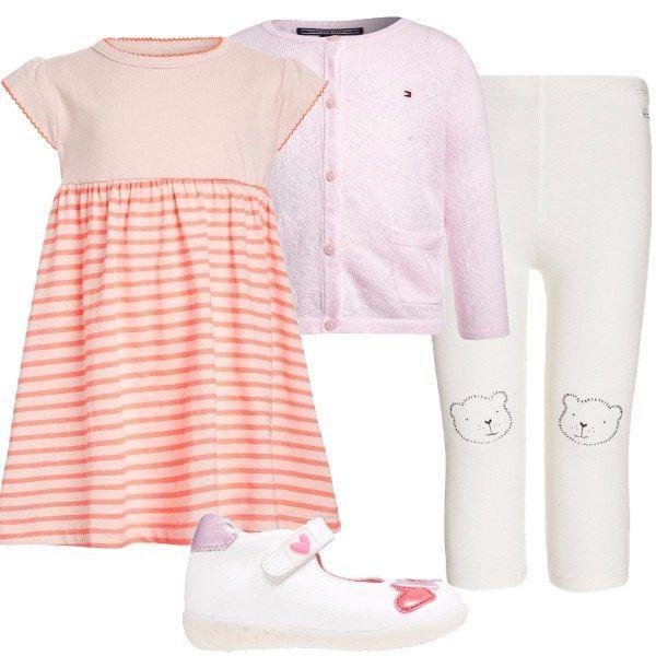 Una neonata baciata dal sole che indossa: abito a maniche corte, rosa a righe, coperto dal cardigan rosa in cotone, griffato Tommy Hilfiger, leggings bianchi e scarpe bianche con cuori.
