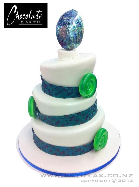 Wedding cake with paua (abalone) shell on top, edible green koru ferns and woven flax ribbon around the tiers.... love love love!