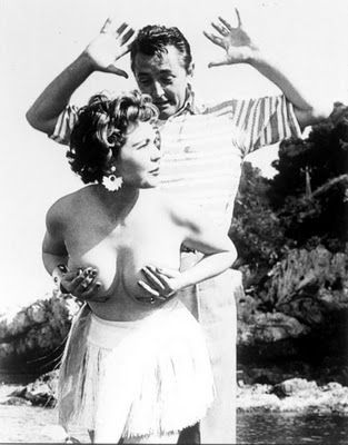 Robert Mitchum freaking out after up-and-coming starlet, Simone Silva, removes her top during a photo shoot. At the time, Robert was in France with his wife on a romantic trip to help make up for all his recent playboying. LOL