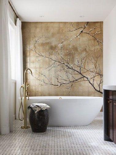 Une déco de salle de bain digne d'un espace consacré au bien-être avec au dessus de la baignoire blanche une fresque réalisée sur un mur de carreaux de verres peint dans des tons mordoré et brun. Le panier en osier et le robinet baignoire îlot complètent à ravir l'ambiance de cette salle de bain hyper zen